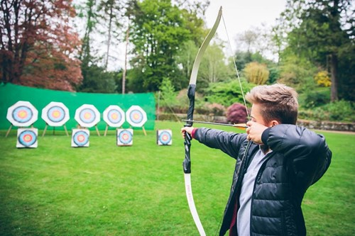 A child shooting a bow and arrow doing archery at Brockhole on Windermere